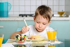 Ragazzo che mangia alla tavola, esaminante l'orizzontale del piatto Fotografia Stock