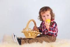 Ragazzo che mangia aplle giallo. fotografia stock