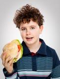Ragazzo che mangia grande panino Fotografia Stock Libera da Diritti