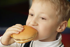 Ragazzo che mangia hamburger Fotografia Stock Libera da Diritti
