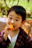 Ragazzo che mangia loquat Fotografie Stock Libere da Diritti