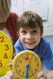 Ragazzo che mostra orologio giallo con l'insegnante In Background Immagini Stock Libere da Diritti