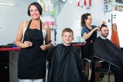 Ragazzo che ottiene capelli tagliati dal parrucchiere della donna Immagine Stock