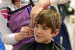 Ragazzo che ottiene un taglio di capelli fotografie stock