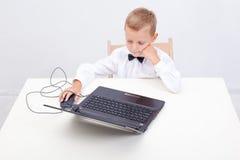 Ragazzo che per mezzo del suo computer portatile Fotografia Stock