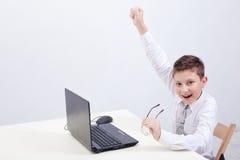 Ragazzo che per mezzo del suo computer portatile Immagine Stock