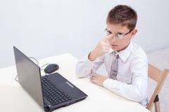 Ragazzo che per mezzo del suo computer portatile Fotografie Stock