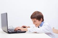 Ragazzo che per mezzo del suo computer portatile Fotografie Stock Libere da Diritti