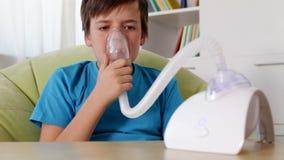 Ragazzo che per mezzo dell'inalatore del nebulizzatore - tossendo stock footage