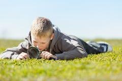 Ragazzo che per mezzo della lente d'ingrandimento sopra il campo di erba Fotografia Stock