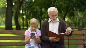 Ragazzo che per mezzo dello smartphone mentre libro di lettura del nonno, concetto di tecnologia contro carta stock footage