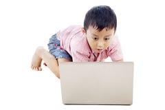 Ragazzo che per mezzo seriamente del computer portatile Fotografia Stock Libera da Diritti