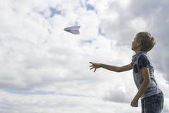 Ragazzo che pilota un aereo di carta contro il cielo blu immagine stock