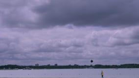 Ragazzo che pilota un aquilone sulla spiaggia al cielo tempestoso archivi video