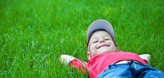 Ragazzo che pone sull'erba. Picnic della famiglia in la sosta di primavera Fotografie Stock Libere da Diritti