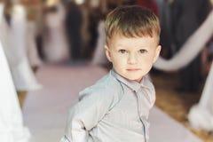 Ragazzo che porta camicia classica che sta nella chiesa durante la cerimonia di nozze Fotografia Stock