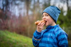 Ragazzo che porta un rivestimento blu della pioggia che mangia hot dog all'aperto Fotografie Stock