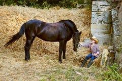 Ragazzo che posa con un cavallo dopo l'allenamento ranch Fotografia Stock