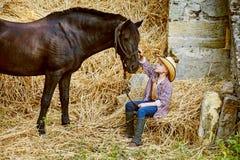 Ragazzo che posa con un cavallo dopo l'allenamento ranch Fotografia Stock Libera da Diritti