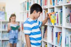 Ragazzo che prende un libro dallo scaffale per libri in biblioteca Fotografia Stock