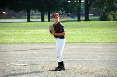 Ragazzo che prepara lanciare dentro il gioco di baseball della gioventù Immagini Stock