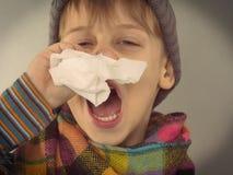 Ragazzo che pulisce il suo naso Immagine Stock