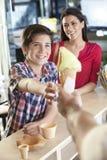 Ragazzo che riceve il cono del gelato alla vaniglia dal venditore tramite la madre immagini stock
