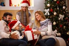 Ragazzo che riceve il regalo di Natale in grande scatola dai genitori Immagine Stock