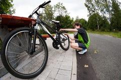 Ragazzo che ripara bici sulla pista Fotografia Stock