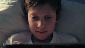 Ragazzo che riposa nel suo letto nella sera facendo uso della sua compressa digitale archivi video
