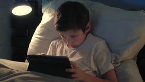 Ragazzo che riposa nel suo letto nella sera facendo uso della sua compressa digitale stock footage