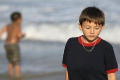 Ragazzo che ritiene triste alla spiaggia fotografia stock