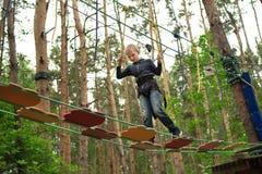 Ragazzo che scala al parco di avventura fotografia stock