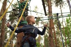 Ragazzo che scala al parco di avventura fotografia stock libera da diritti