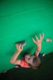 Ragazzo che scala sulla parete verde Fotografie Stock