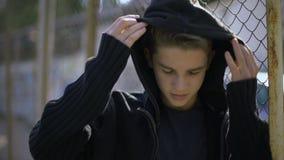 Ragazzo che si appoggia recinto, maglia con cappuccio d'uso, orfano nel collegio, relegazione archivi video