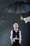 Ragazzo che si leva in piedi sotto l'ombrello in pioggia Fotografie Stock Libere da Diritti