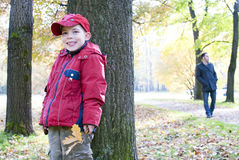 Ragazzo che si nasconde dietro un albero dal suo papà Immagine Stock Libera da Diritti