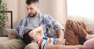 Ragazzo che si rilassa sul rivestimento del padre e sulla storia d'ascolto del libro elettronico video d archivio