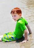 Ragazzo che si siede in acque basse Fotografie Stock Libere da Diritti