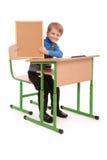 Ragazzo che si siede ad uno scrittorio della scuola e che tiene bordo Immagine Stock
