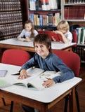 Ragazzo che si siede alla Tabella con i libri con i compagni di classe dentro Immagini Stock Libere da Diritti