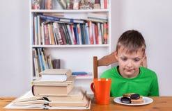 Ragazzo che si siede alla tavola e che fissa ai biscotti Fotografia Stock Libera da Diritti
