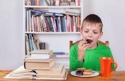 Ragazzo che si siede alla tavola ed e che mangia i biscotti Fotografie Stock Libere da Diritti