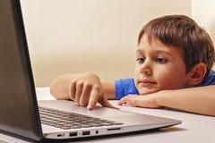 Ragazzo che si siede allo scrittorio con il computer portatile e gioco guardante, che passa in rassegna video o immagine stock