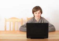 Ragazzo che si siede con un computer Fotografie Stock Libere da Diritti