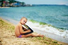 Ragazzo che si siede con un computer portatile sulla spiaggia Fotografie Stock