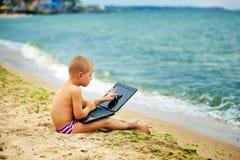 Ragazzo che si siede con un computer portatile sulla spiaggia Fotografia Stock Libera da Diritti