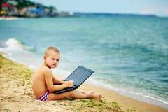 Ragazzo che si siede con un computer portatile sulla spiaggia Fotografie Stock Libere da Diritti