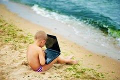 Ragazzo che si siede con un computer portatile sulla spiaggia Fotografia Stock
